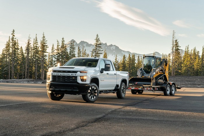 A white 2020 Chevrolet Silverado 2500HD Custom pickup truck, towing another vehicle on a mountain road