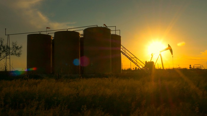 An oil pump and storage tanks with the sun rising in the background