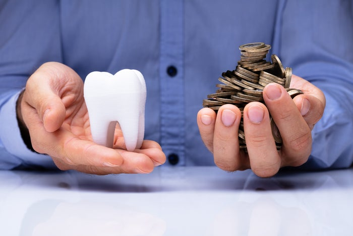 Man holding a large tooth model in one hand and a pile of coins in the other hand