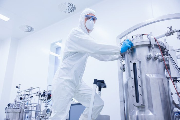 A technician servicing a stainless steel bioreactor used in drug manufacturing.