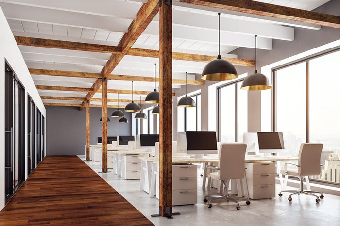 An empty office with exposed wood beams and modern furniture.