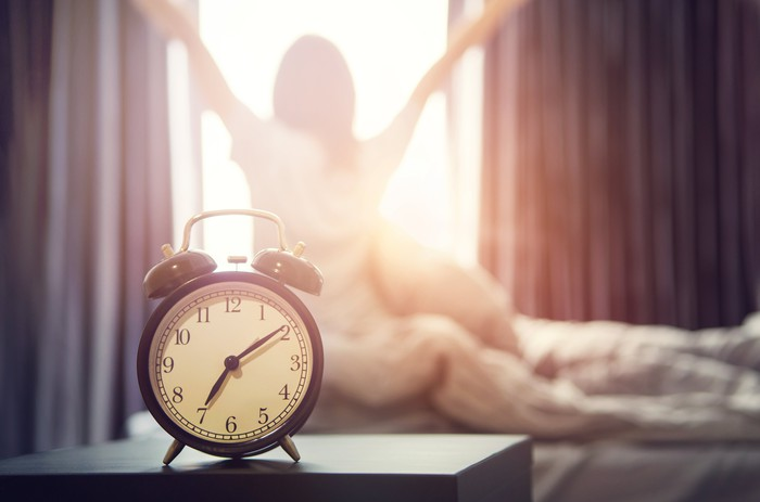 A woman rises to the sound of an alarm clock