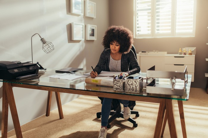 Woman taking notes at desk in home office
