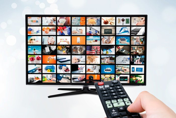 Hand holding a TV remote control pointing at a digital TV with many images/channels shown on menu.