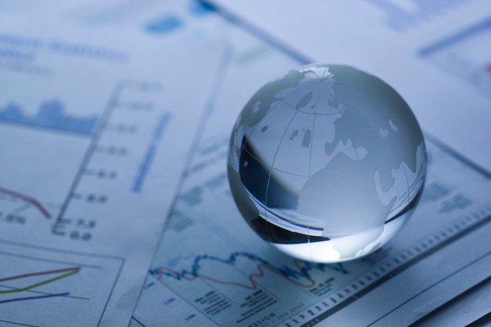 A small glass globe on top of papers displaying graphs and charts