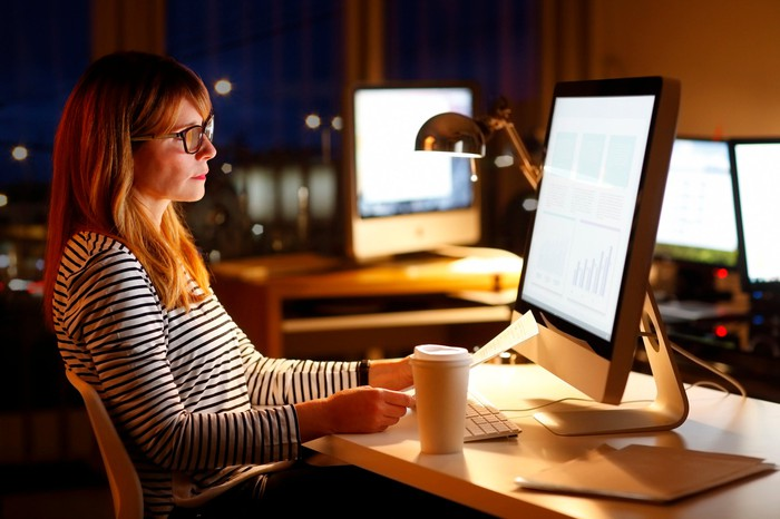 Woman sitting in front of a computer in an office at night