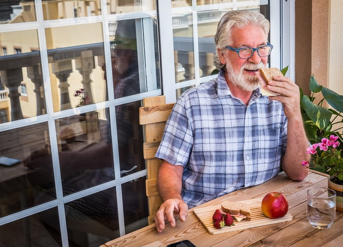 Older man holding a sandwich to his mouth