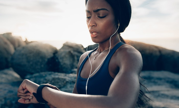 A young woman checks her fitness tracker while running outside.