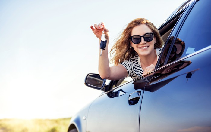Happy woman sitting in car holding car keys.