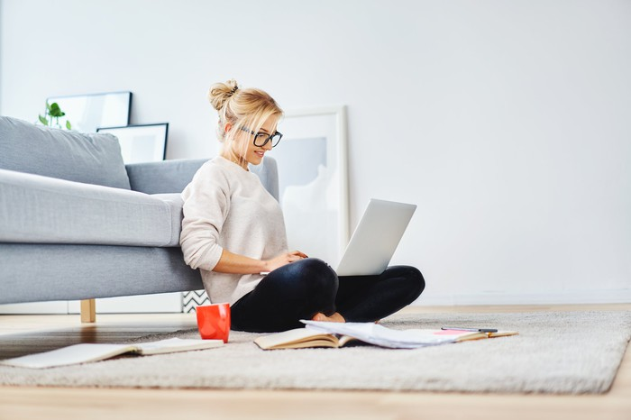 Woman sitting on floor up against couch, typing on laptop.