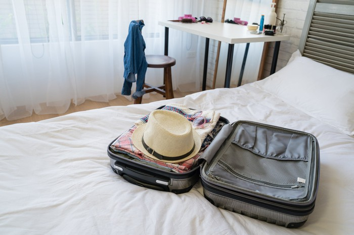 Packed open suitcase with straw hat on top sitting on bed