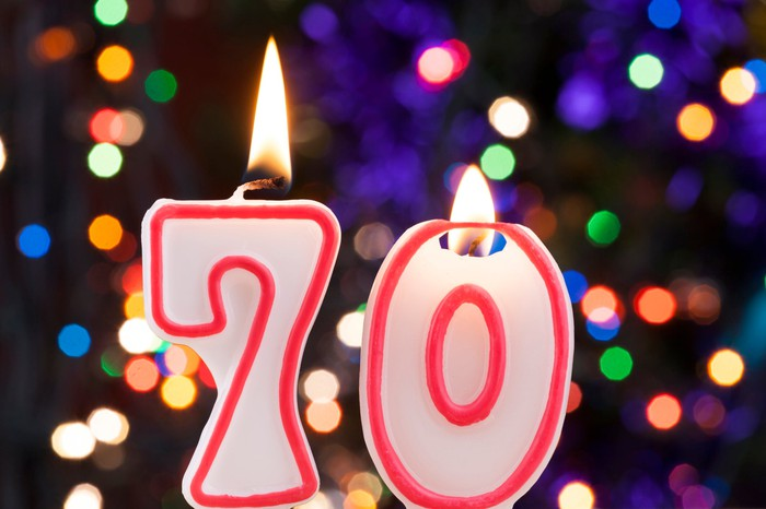 We see two candles on a birthday cake - spell number 70.