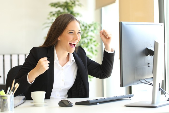 A woman in business attire cheering in front of a computer screen.