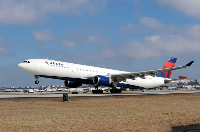 A Delta Air Lines plane landing on a runway.
