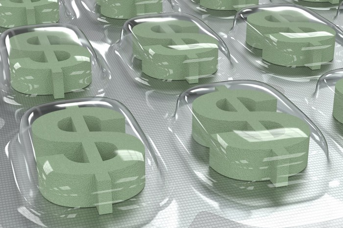 Pills shaped as dollar signs in pill packaging