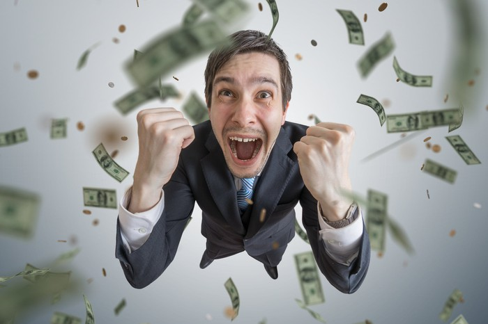 Man looking up and cheering as money falls around him.