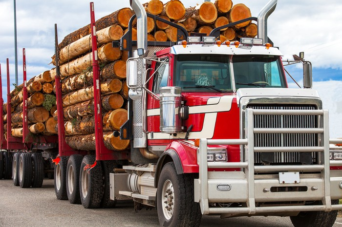 Truck hauling logs from a job site.