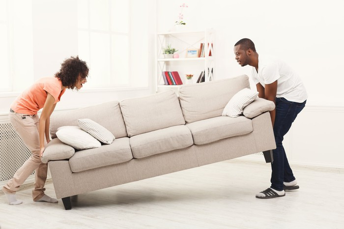 A man and woman move a sofa into position in a large living area.