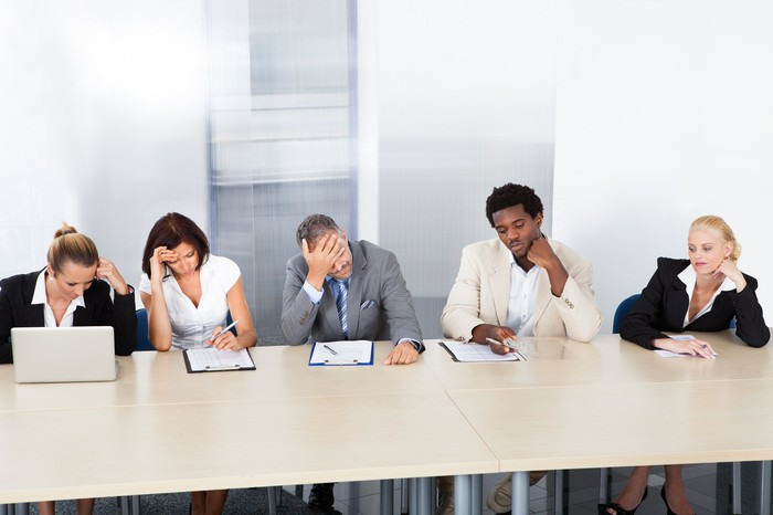 Five businesspeople in a meeting, looking upset