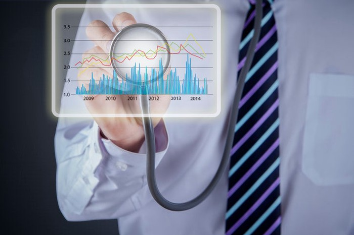A man in a tie holding up a stethoscope to a stock chart.