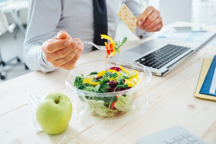 Man eating salad at desk while sitting at laptop