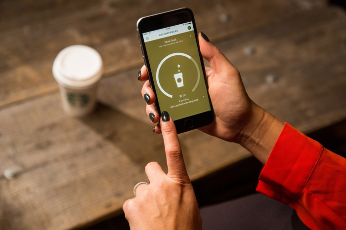 A woman using the Starbucks' mobile loyalty program on her smartphone.