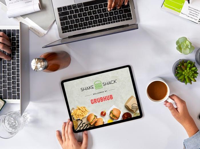 A tablet displaying Shake Shack and Grubhub's logos.