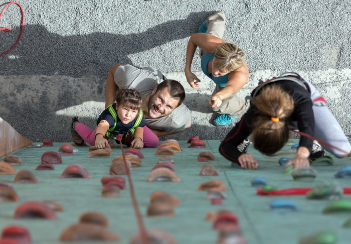 A family moving up a climbing wall.