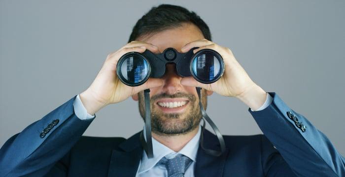 A businessman looks through a pair of binoculars.
