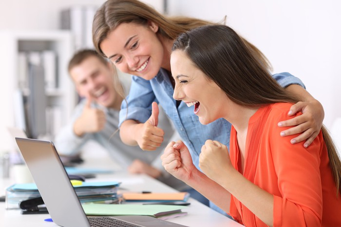 Two smiling office workers give thumbs-up encouragement to a colleague, who is cheering at her laptop.