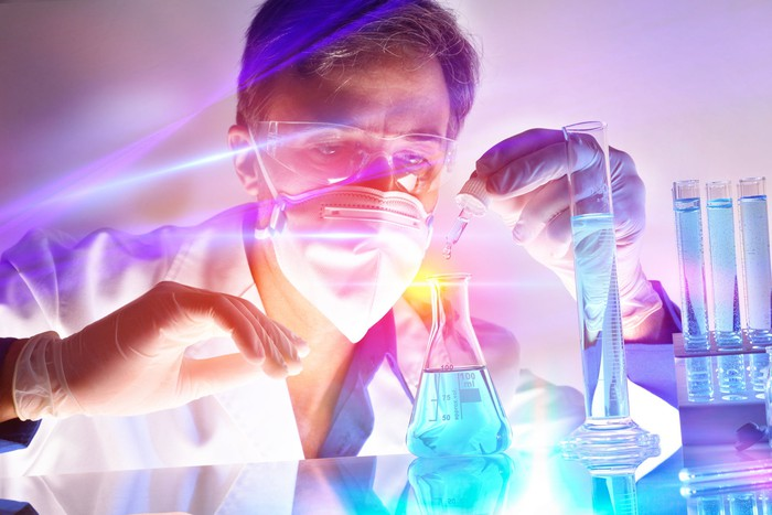 Man in lab coat, goggles, and face mask working with a beaker and test tubes.