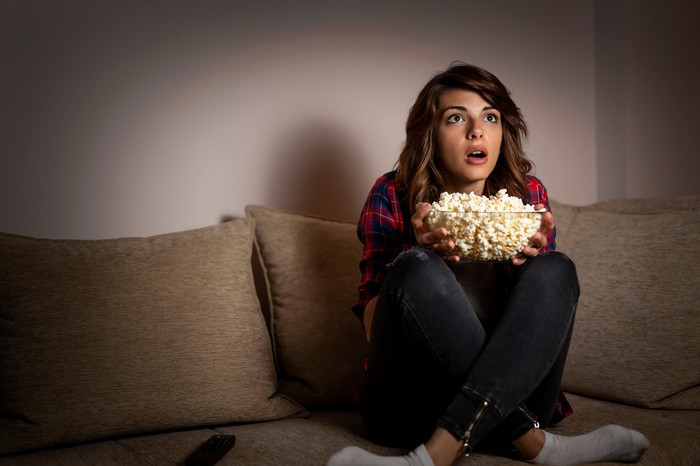 A girl sitting on a couch with a bowl of popcorn.