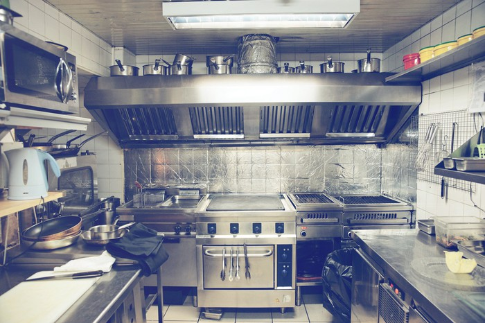 Forlorn looking commercial kitchen with an oven in the center