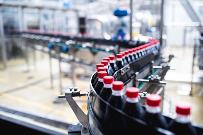 Soda bottles on a curving conveyor belt in a bottling plant.