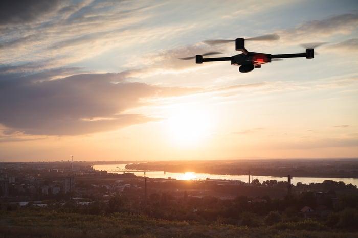 Quadcopter drone set against a sunrise scene