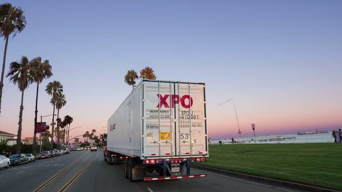 An XPO semitruck driving along a coastal road.