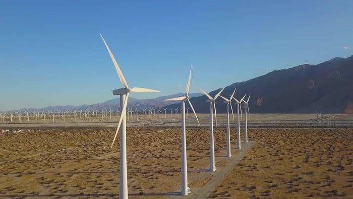 Row of a couple dozen wind turbines in a desert.