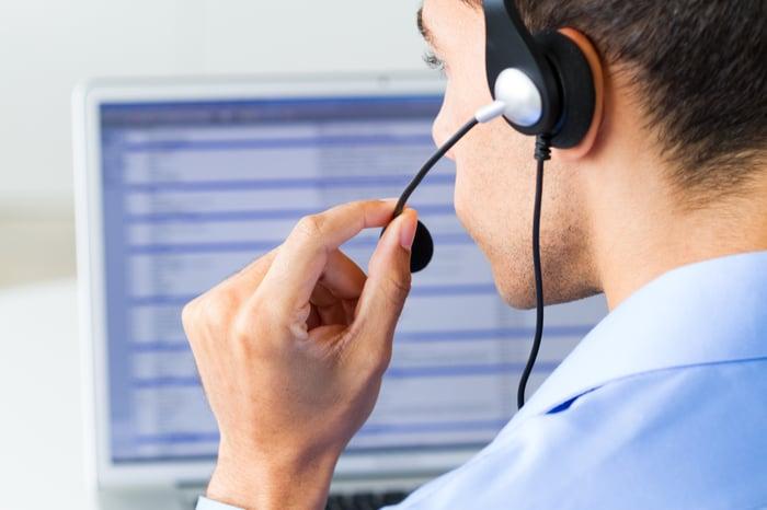 A customer service representative talks on a headset.