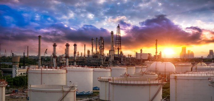 A chemical plant in front of a setting sun.