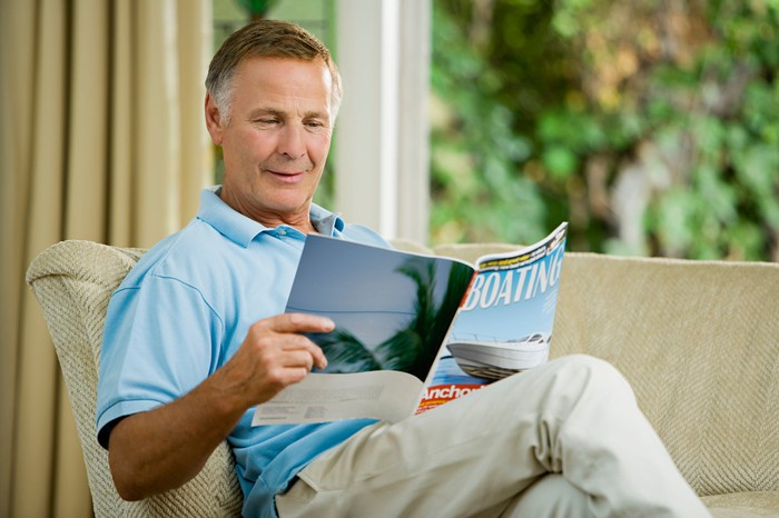 Older man sitting on couch reading boating magazine