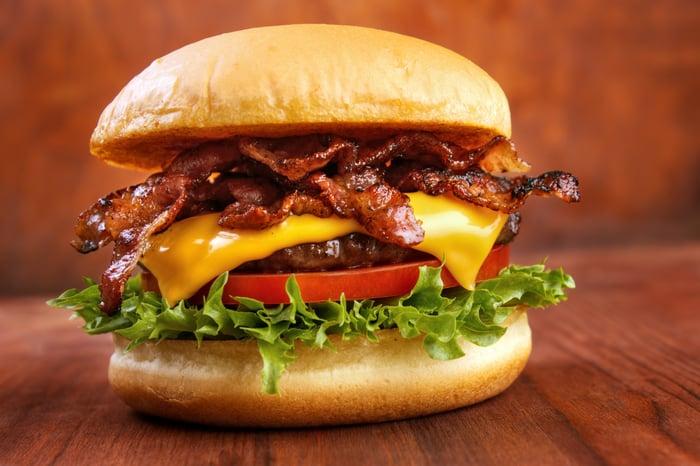 Bacon cheeseburger atop a table.