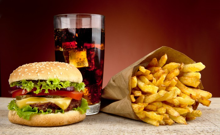 A cheeseburger, soft drink, and a bag of french fries lying on a table.