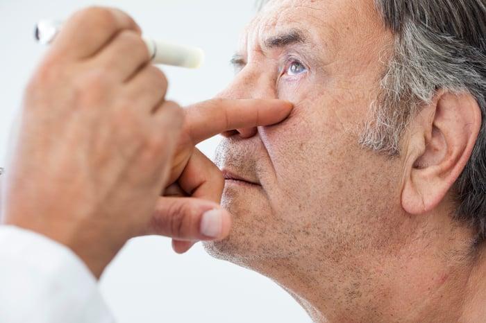 An elderly white male undergoing an eye examination.
