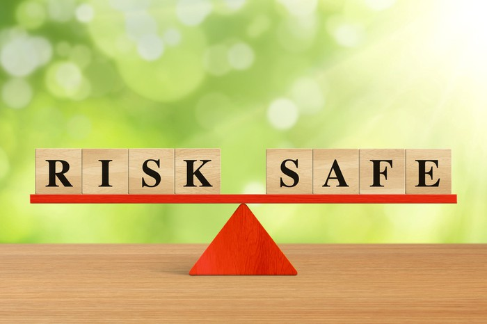 The words risk and safe spelled out in wooden block letters being balanced on a red seesaw sitting on a wooden table.