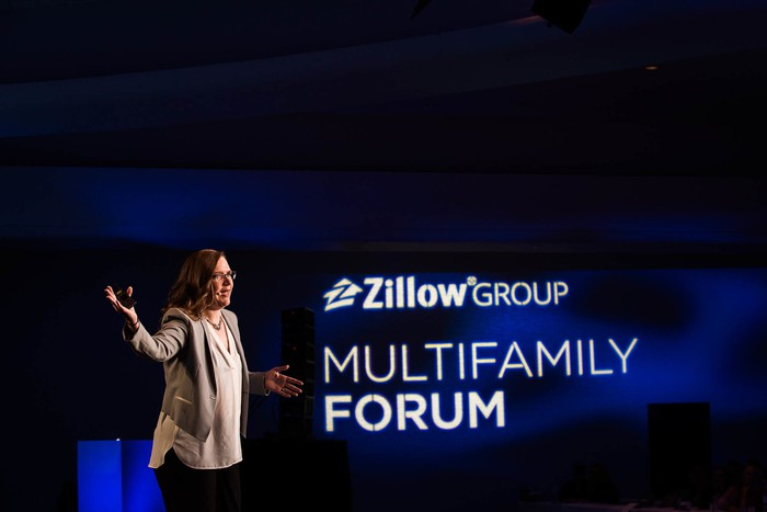 Speaker in a room with deep blue lights, with Zillow Group logo superimposed.