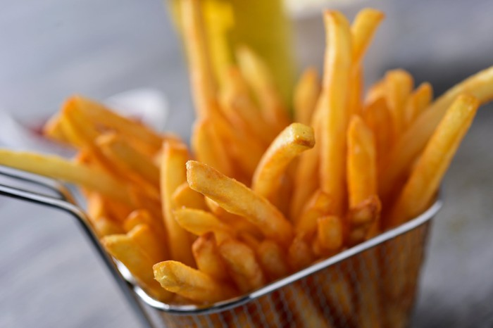 Golden french fries in a small wire basket.