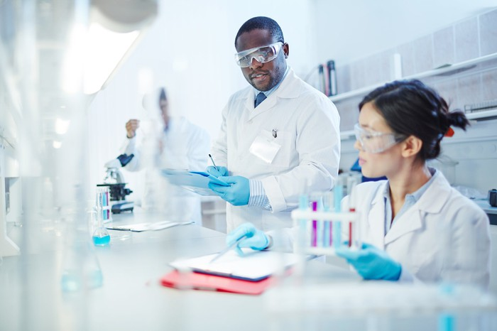 Two people in lab coats and safety goggles working in a lab.