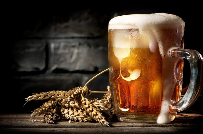A large, overflowing glass of beer with a stem of wheat lying on a table.