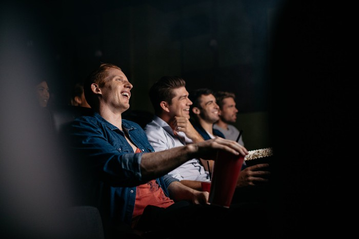 A row of men in a movie theater, with one reaching for his popcorn