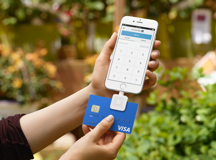 A Square credit-card reader attached to a smartphone.